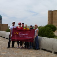 PWP students proudly display the USC Dornsife banner, with the Mausoleum of Khoja Ahmed Yasawi in the background.