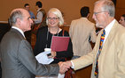 Lee Crystal (MLS '12) shakes hands with Jim Kincaid (right), Aerol Arnold Chair in English and Professor of English, and chair of the MLS Faculty Board in USC Dornsife, after Crystal presented his research at the international symposium. Nita Kincaid looks on. Photo by Emily Loynachan.