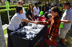USC Dornsife senior Jasmine Torres greets a young student at the Trojan Guardians Scholarship Program (TGS) booth during the Sept. 28 College Within Reach event on the University Park campus. Photo by Erica Christianson.