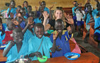 International relations alumna Molly Beckert sits with students during lunchtime at the Awoo Primary School in Gulu, Uganda. Echoing Good, the nonprofit Beckert founded, raised funds to create a farm and lunch program at the school. Photos courtesy of Molly Beckert.