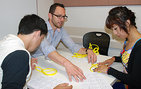 USC Dornsife's Aaron Lauda of mathematics teaches high school senior Jailyne Olvera and another student how to solve the knot theory game he developed to show students how mathematical knowledge is developed and processed. Photo by Susan Bell.