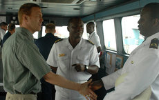 USC Dornsife alumnus Augustus Vogel (left) meets members of the Ghana Navy aboard a U.S. vessel during Vogel's work with U.S. Naval Forces Africa. U.S. Navy photo by Mass Communication Specialist 2nd Class Michael Campbell.