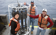 From left, doctoral student Diane Kim, SPOT coordinator Troy Gunderson and doctoral student David Needham stand aboard research vessel <em>Yellowfin</em> with a Rosette water sampler equipped with sensors used to collect real-time environmental data. Photo by Cheryl Chow.