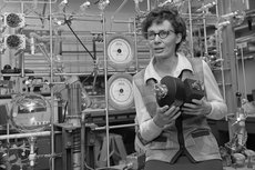 Virginia Carter in 1972 in her Aerospace Corporation lab holding a device to measure air density. The device would be bolted to a satellite, which circled the Earth, yielding data to improve the guidance of satellites. Photo courtesy of the  the <em>Los Angeles Times</em> photographic archive, UCLA Library.