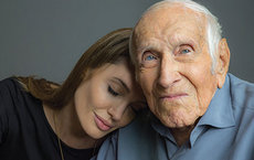 Alumnus Louis Zamperini is honored in the newly launched Louis Zamperini Scholarship. Here, the late Zamperini shares a moment with Angelina Jolie, who directed the upcoming film <em>Unbroken</em> about his life. Photo courtesy of Universal Pictures.
