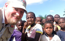 As one of the government's most experienced disaster response experts, alumnus Ben Hemingway led the battle against the deadly Ebola virus in Liberia, where he is seen with local residents. Photos courtesy of Ben Hemingway.