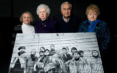Survivors at the event stand with an enlargement of the iconic photograph taken of them on Jan. 27, 1945. From left are Paula Lebovics, Miriam Ziegler, Gabor Hirsch and Eva Kor. Photo courtesy of Ian Gavan/Getty Images.