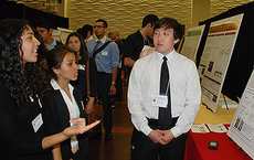 High school student and future USC Dornsife chemistry major Belen Espinoza, far left, asks senior Thomas Do a question about his research project. Photos by Susan Bell.