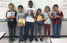 Young students from James A. Foshay Learning Center pose with the new books they received as holiday gifts from their USC student tutors. Photos courtesy of Tina Koneazny.