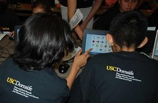 Proudly sporting USC Dornsife's Young Scientists t-shirts, two young participants in the program learn basic coding during the computer science and robotics workshop held April 6 at 32nd Street USC Performing Arts Magnet. Photos by Susan Bell.