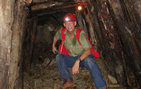 Jeffrey Wilson '76 sits atop mined rock in an under- ground gold mine during a June 2006 expedition in Hunan Province, China. The amount of timber used to shore up the walls and high humidity are indicative of the unstable ground and poor ventilation. Photo courtesy of Jeffrey Wilson.