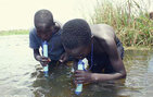 Two boys use LifeStraws, instant microbiological water purifiers, while drinking out of a lake in Africa. Photo courtesy of Water Solutions for Life.