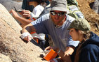 Scott Paterson, professor of earth sciences in USC College, shows a student how to use a Brunton compass to measure rocks that have aligned minerals or layering, during a recent trip in Yosemite National Park. Photo courtesy of Scott Paterson.