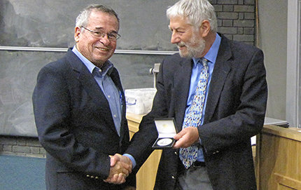 Arieh Warshel, Distinguished Professor of USC Dornsife (left), receives his  2012 Soft Matter & Biophysical Chemistry Award from the Royal Society of Chemistry's Faraday Division Council President Graham Hutchings during a recent three-day symposium in England. Photo courtesy of the Royal Society of Chemistry.