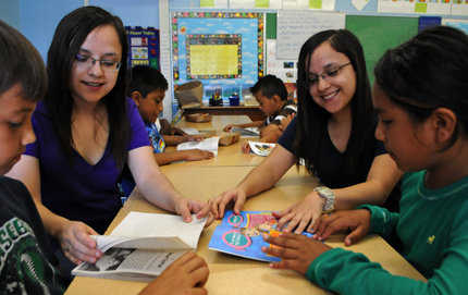 USC Dornsife undergraduate twins Jazmin (left) and Cynthia Vidana teach children to read through the Joint Educational Project (JEP). Photo by Carlos Puma.