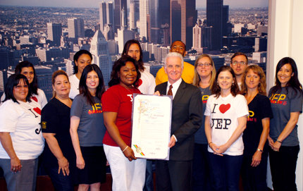 Flanked by Joint Educational Project (JEP) staff, volunteers and former volunteers, Los Angeles City Councilman Paul Krekorian (front right) holds up the JEP resolution with JEP Executive Director Tammara Anderson at the May 3 Los Angeles City Council Meeting. The resolution honors JEP's 40-year history of service learning at USC and in the L.A. community. Photo by Laura Paisley.
