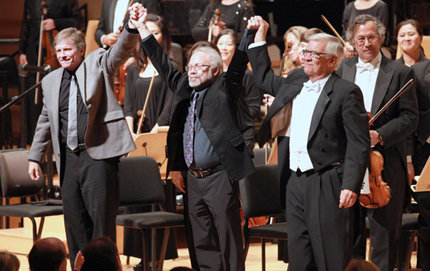 From left: Frank Ticheli of USC Thornton School of Music, David St. John of USC Dornsife and John Alexander, artistic director of the 140-voice chorale and the Pacific Symphony, link hands and take a bow. They received an outpouring of emotion from the audience with three curtain calls at their premiere of <em>The Shore</em> at the Segerstrom Center for the Arts. Photo by Andy Templeton.