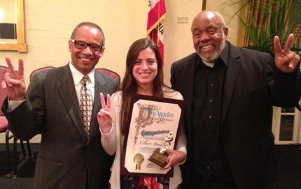 Flanked by Michael L. Jackson (left) and Bennie Davenport of Blazer, USC Dornsife's Claire Baugher holds up her 2013 Extraordinary Engagement Award during the awards ceremony. Photo courtesy of Claire Baugher.