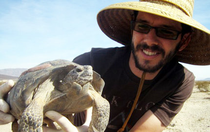 USC Dornsife graduate student Michael Tuma, seen here holding up a Mojave Desert tortoise, wants to ensure that tortoises have the space they need to thrive. Photo courtesy of Michael Tuma.