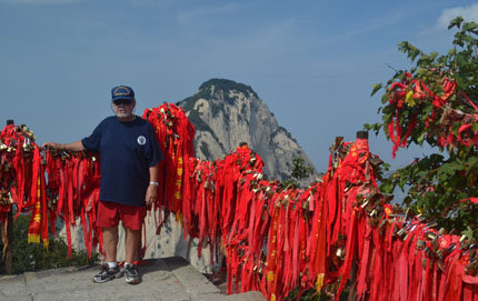 USC Dornsife alumnus Bill Altaffer is among the most traveled people in the world. He has exhausted 12 passports and 130 visas, visiting all 192 United Nations countries plus 300 island groups. Here he is pictured on the summit of China's Mount Hua Shan surrounded by red Tibetan Buddhist prayer flags. Photo courtesy of Bill Altaffer.