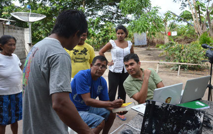 Desano indigenous researchers Marcelino Massa (blue shirt) and Frank Matos (gray shirt) explaining to Dr. Silva (green shirt) the significance of the image on the cover of a book about the Desano myth of origins. Photo Credit: DLDP Team 2013 (c) copyright. All rights Reserved.