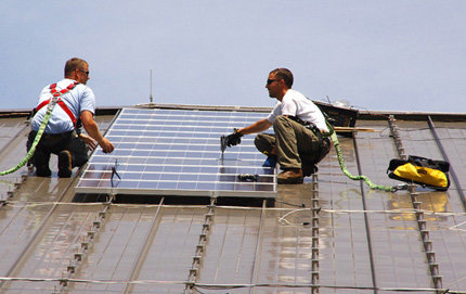 The Program for Environmental and Regional Equity (PERE), housed at USC Dornsife, contributed to reports that ensured low-income communities of color would have access to the benefits of the Los Angeles Department of Water and Power's solar rooftop feed-in tariff program. Workers are seen here installing solar panels on a building. Photo courtesy of Fort Dix/U.S. Army Environmental Command.