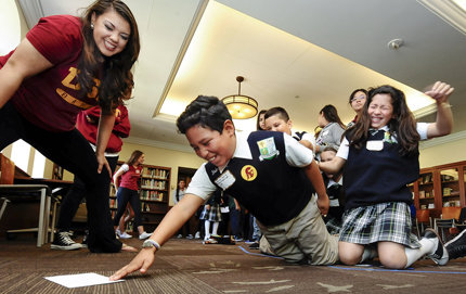 USC senior Christine Burcelis and Resurrection Catholic School fifth graders Jesus Ajiz and Leslie Lopez learn about civic engagement during the Penny Harvest Academy. Photo by Gus Ruelas.