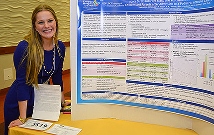 Stephanie Wetzel, a psychology major, with her poster explaining her award-winning research into the relationship between a child's admission to a pediatric intensive care unit and the development of acute stress disorder and post-traumatic stress disorder in the young patients and their families. Photo by Heather Cartagena.