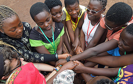 "International relations alumna Rebecca Braun is in the Peace Corps working as a peer educator at a girl's camp in Cameroon. Youths and one volunteer are pictured here making a ""human knot"" as a teamwork exercise. Photo by Rebecca Braun."