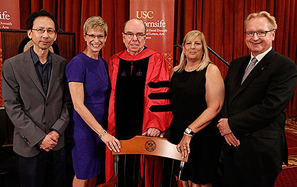 Robert Shrum (center) is presented with a chair bearing the university seal. From left to right: Dennis Chong, chair and professor of political science; Elizabeth Garrett, provost and senior vice president for academic affairs; Shrum; Hope Warschaw, daughter of Carmen and Louis Warschaw; and USC Dornsife Dean Steve Kay. Photos by Steve Cohn.