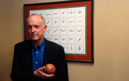 "Shakespeare scholar Bruce Smith stands in front of the ""spatial relations alphabet"" and holds up a clay ball with the same symbols. He uses the unusual alphabet to jolt his students into looking at language differently. Photo credit Taylor Foust."