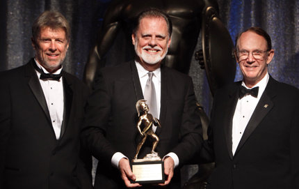 USC College alumnus Taylor Hackford '68 holds up his Asa V. Call Alumni Achievement Award trophy, flanked by USC President Steven Sample (right) and Robert Padgett '68, president of the USC Alumni Association Board of Governors, whom Hackford met while both were students. Photo credit Steve Cohn.