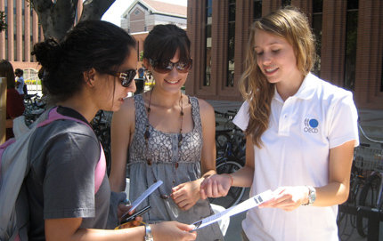 Wearing her OECD T-shirt, Lauren Goodwin (right) chats with students and hands out material about the organization during a development fair she held on University Park campus. Photo credit Monisha Sabnis.
