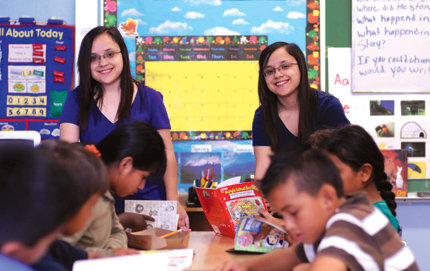 USC College undergraduates Jazmin (left) and Cynthia Vidana teach children to read through the Joint Educational Project (JEP) at Weemes Elementary School, where the twins were once students. Cynthia, three minutes older than her identical twin sister, was tutored by a JEP student when she was a Weemes third grader. Photo credit Carlos Puma.