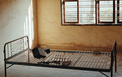 Shackles and torture instruments sit on a rusty iron bed in the Toul Sleng S-21 prison in Cambodia. In some rooms, photographs of the victim found dead in a bed years earlier hang on walls.
